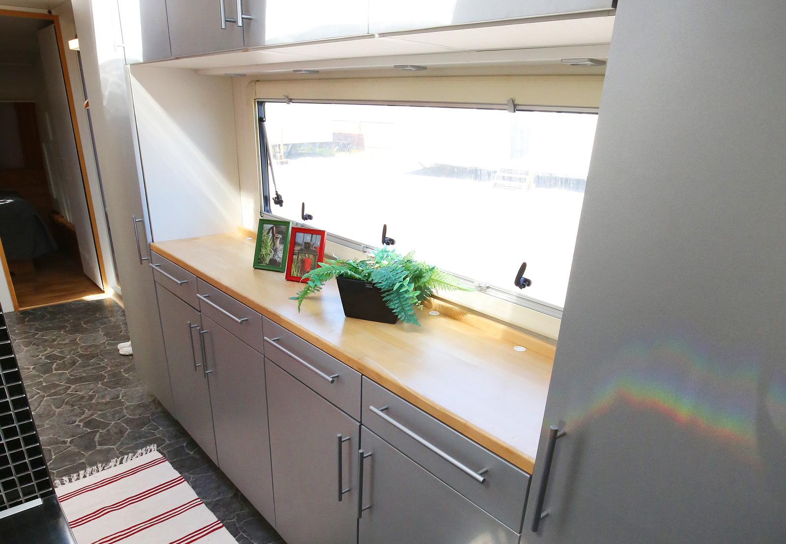 I gången mellan kök och sovrum ryms mycket förvaring och ljusinsläpp via fönster och taklucka. Badrum längs väggen till vänster.