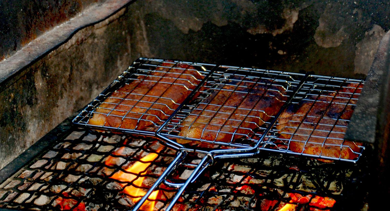 Eldstäderna utmed Sörmlandsleden är ofta murade och försedda med grillgaller. Här grillas fläskkarré till middagen.