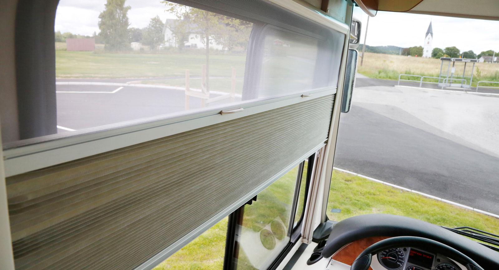 Myggnät och mörkläggning vid hyttens sidofönster.