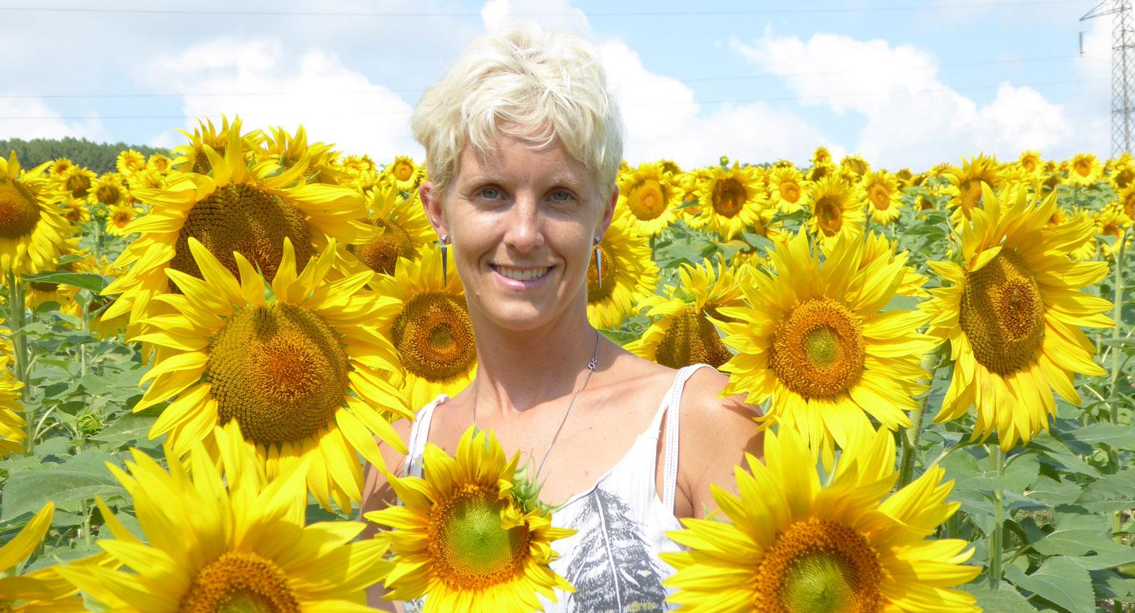 Anna mitt på ett solrosfält i Toskana i norra Italien.