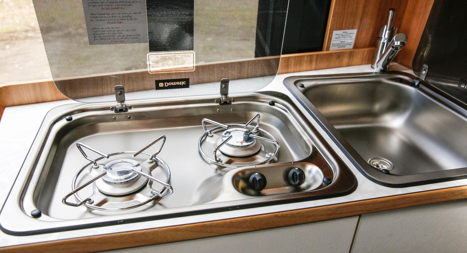 Glaslocken över både spis och vask möjliggör att man kan använda utrymmet till annat. Bänken blir platt och kan till och med täckas med en duk.