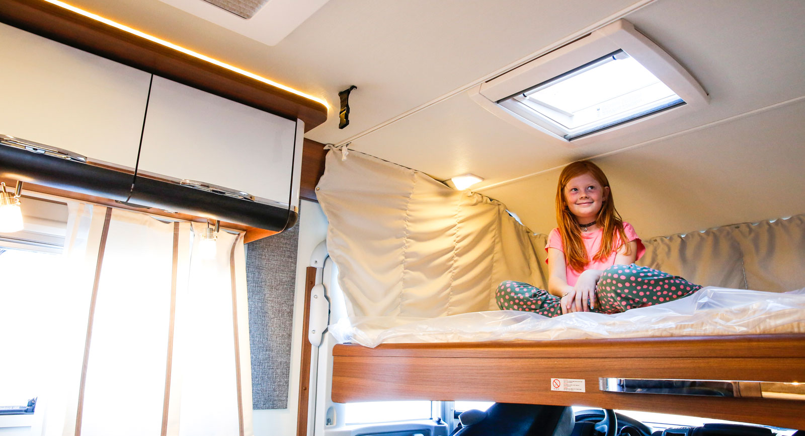 Den takmonterade dubbelsängen i fronten är utmärkt till två barn. Precis som i alla liknande husbilar måste man fälla framstolarna för att kunna fälla ner sängen.