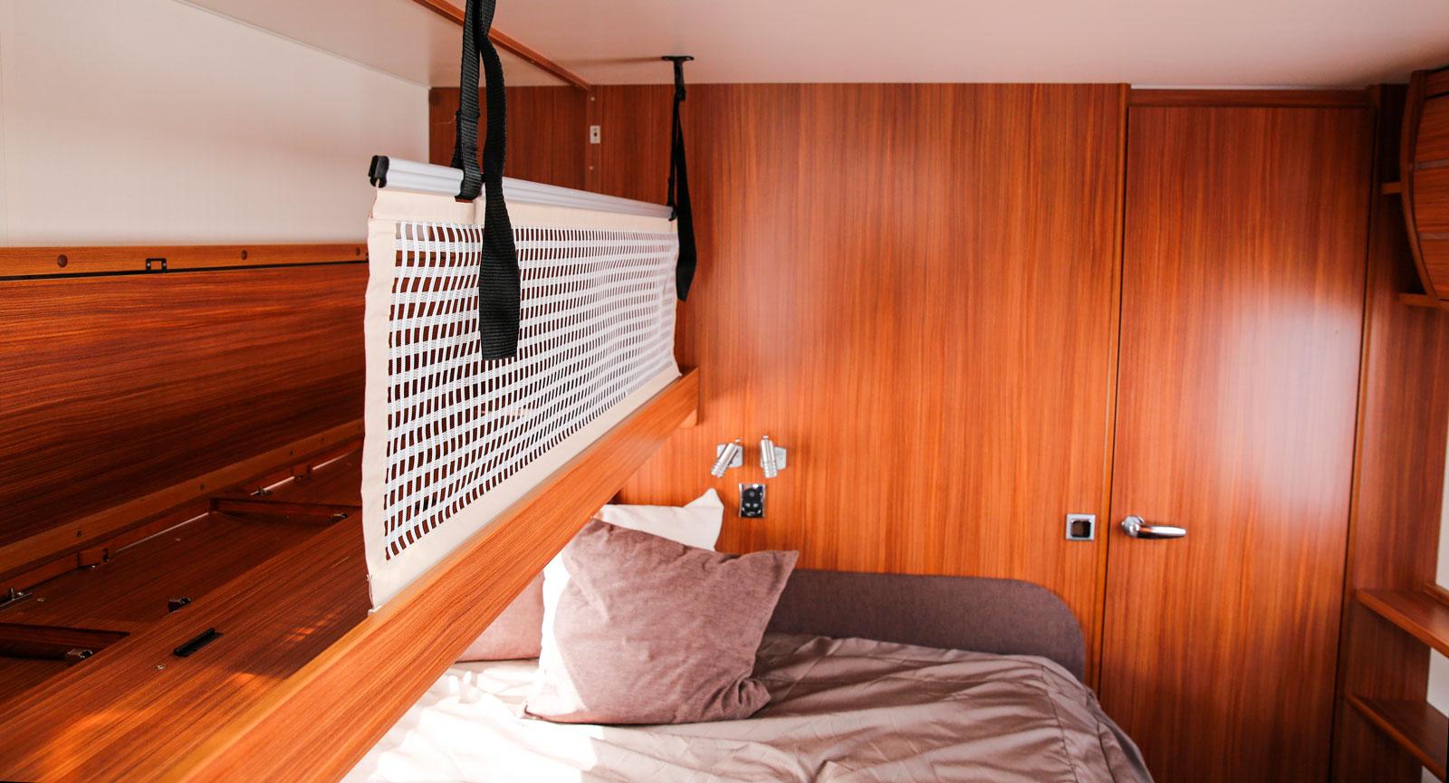 Tre överskåp kan fällas ut över sängen och bilda barnsäng.