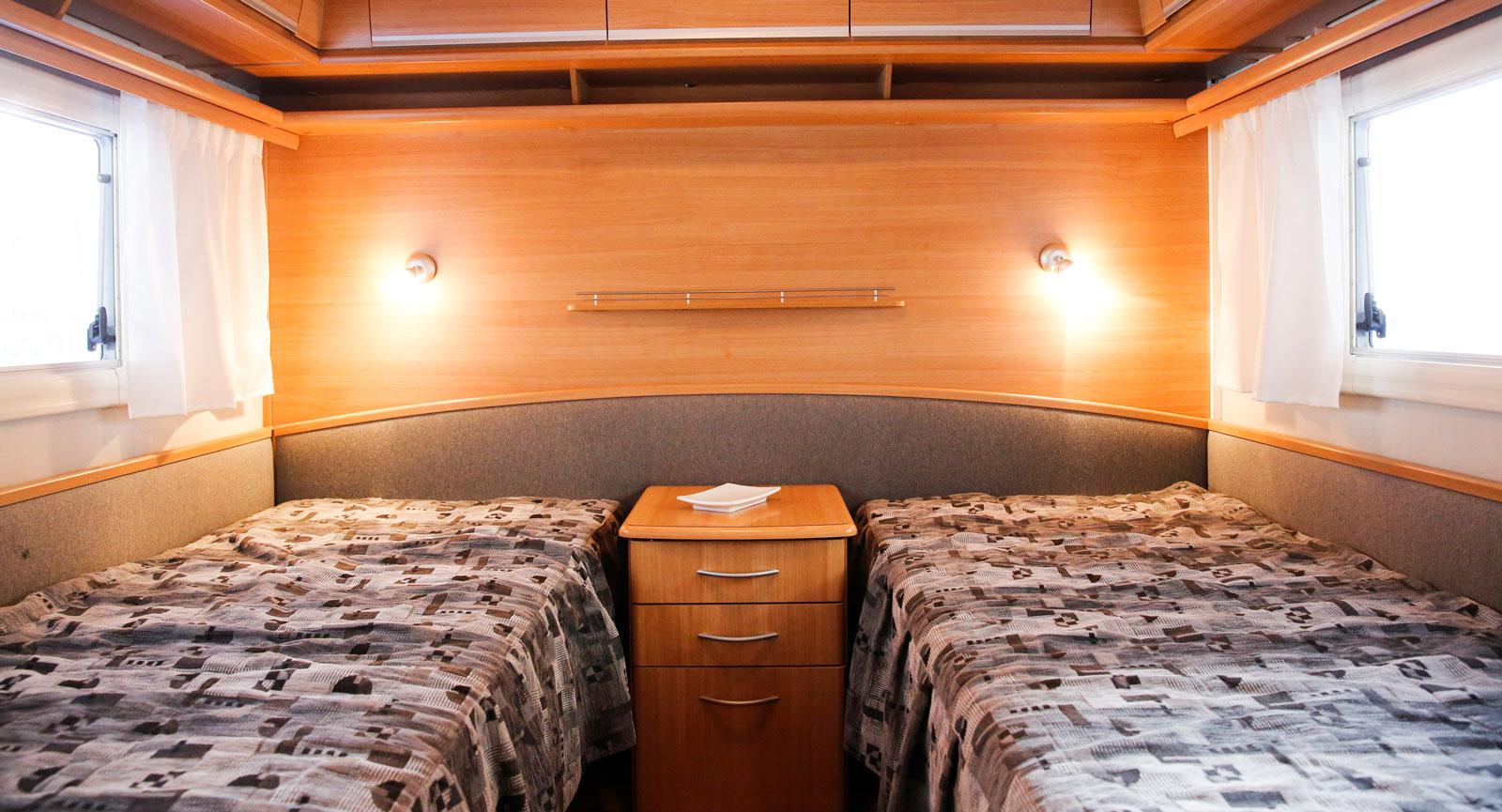 Två längsgående och separata enkelsängar med lådhurts i mitten. Bra läslampor, hyllförvaringar och distansskivor mot väggen.