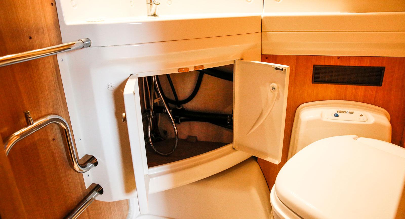 Förvaringen i badrumsskåpet får samsas med slangar och rör.