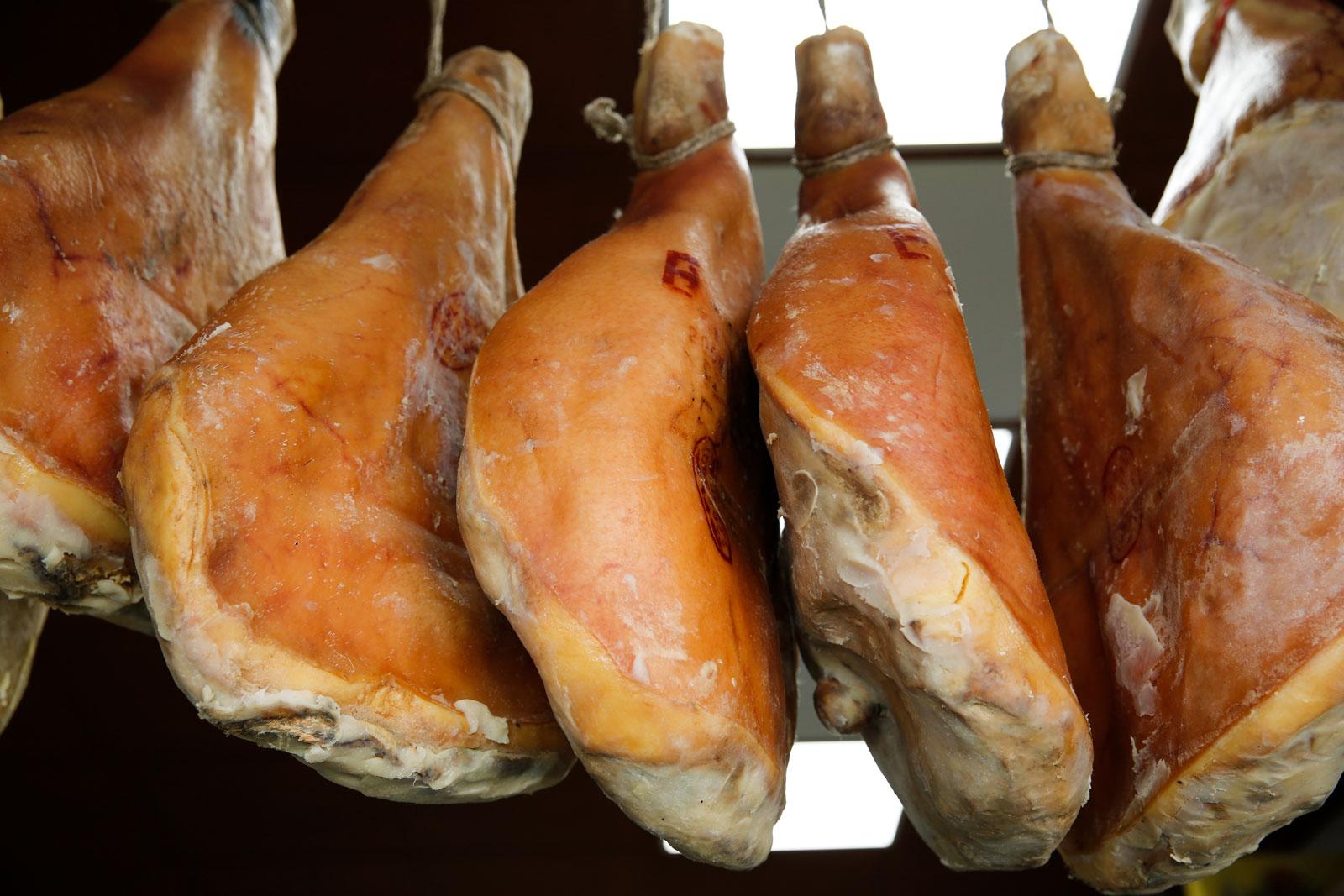 Lufttorkad skinka hänger i taken lite varstans i Italien.