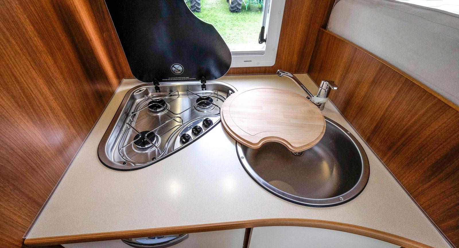 Köket har trelågig spis och rund diskho med täcksiva.