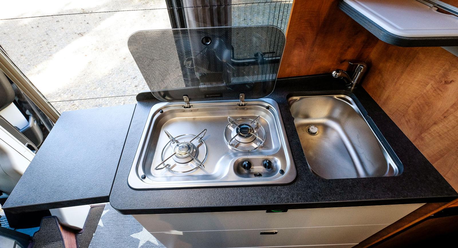 Litet men funktionellt kök. Täckplattan över diskhon blir hylla till höger.
