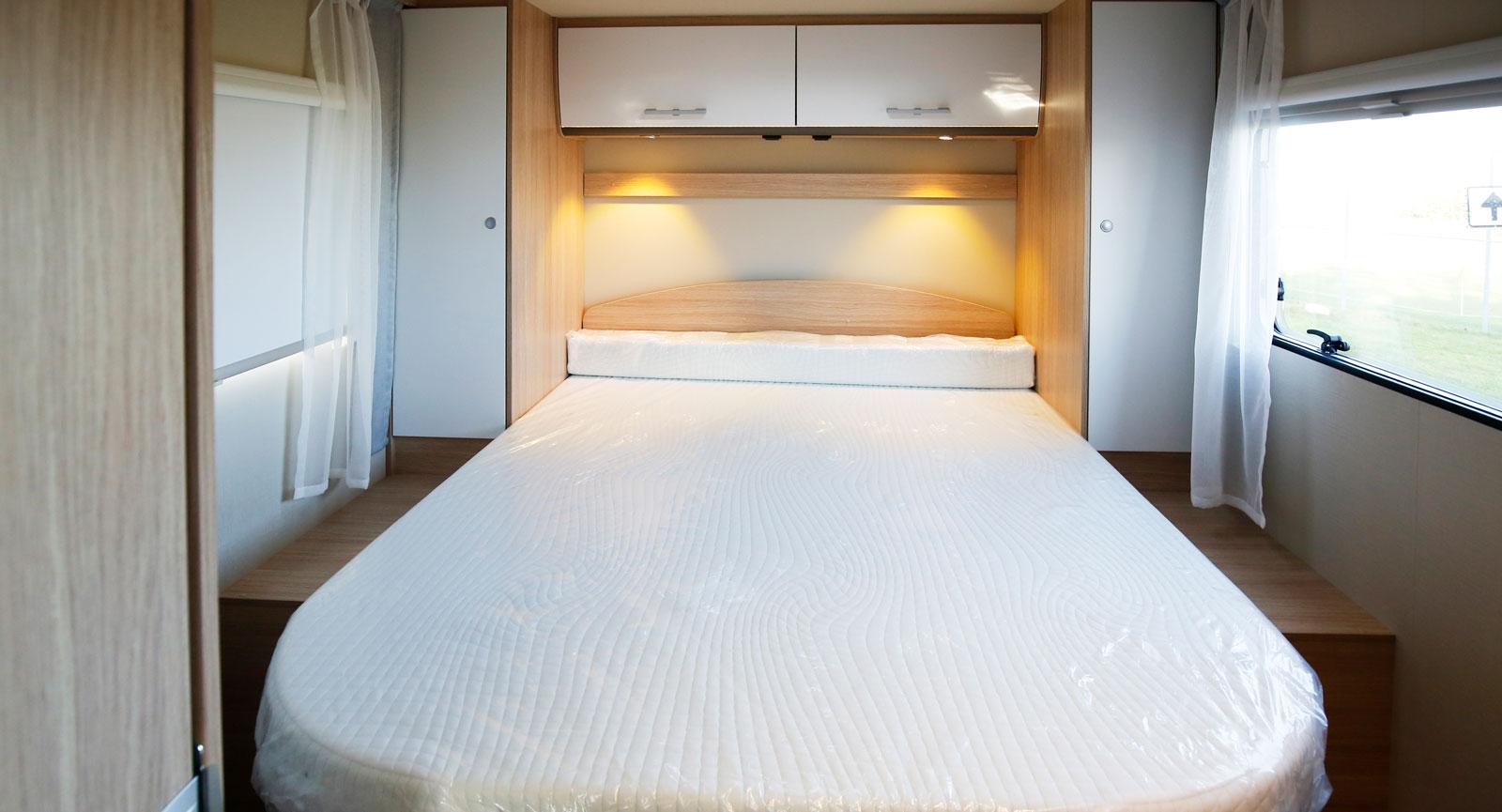 Varsitt högskåp – med belysning – på båda sidor om sängen.