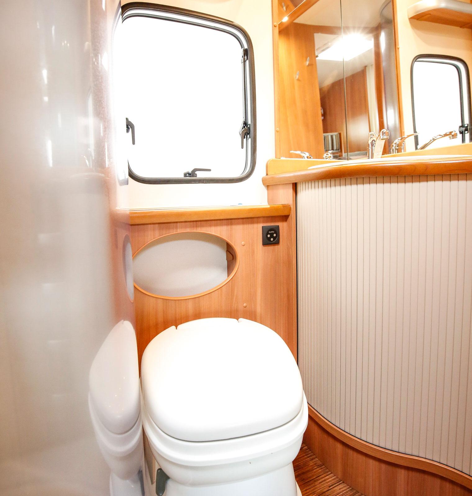 Ljus och rymlig toalett. När glasdörren till duschkabinen är öppen blir det betydligt mer plats runt toaletten.