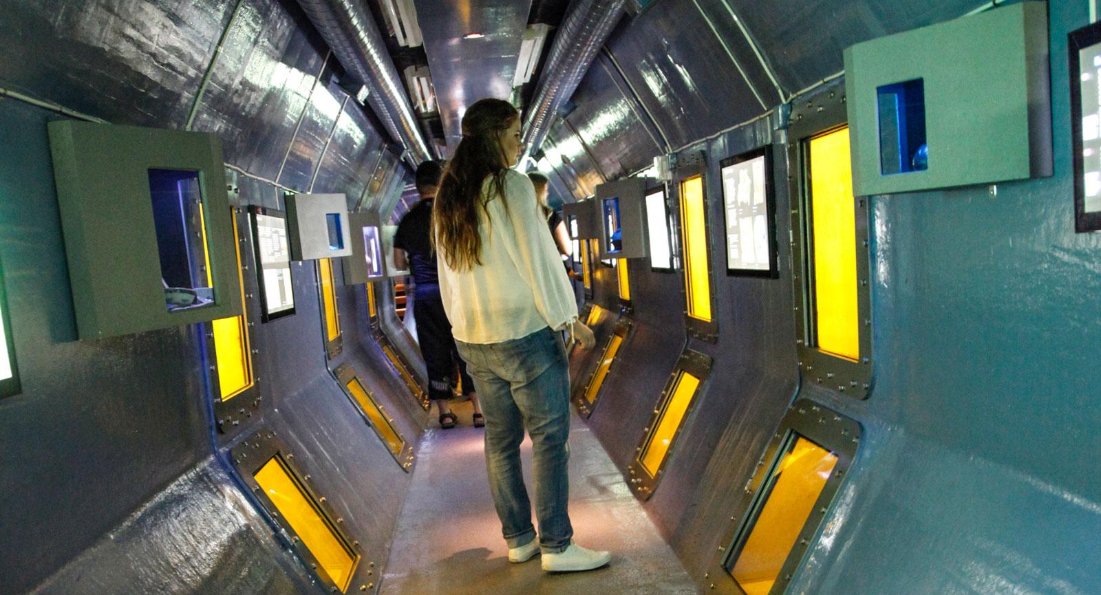 Undervattenstunnel där du kan skymta ett vrak utanför.