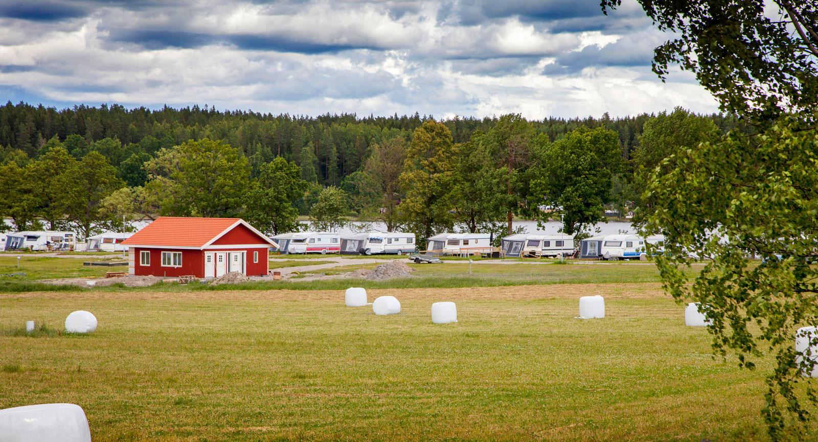 Campingplatserna sedda från åkern med servicehuset i rött.