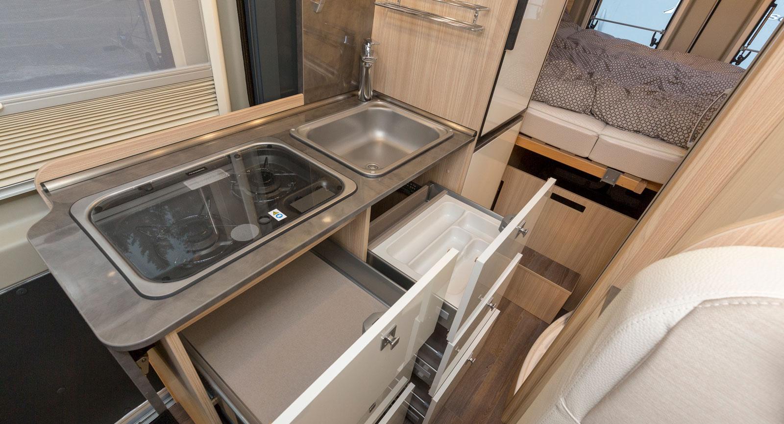 Välutrustat kök med många lådor och kylskåp i rätt höjd.