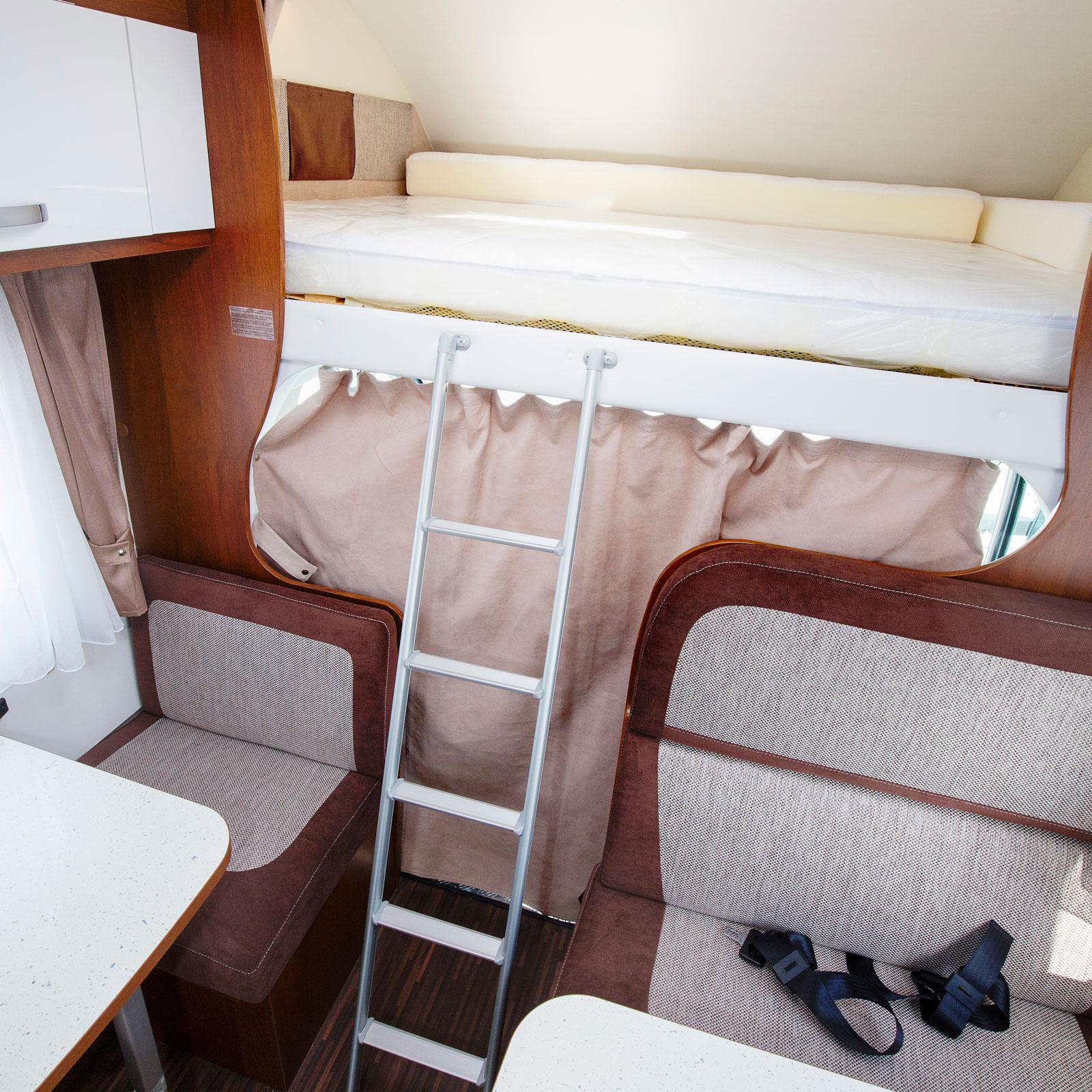 Stegen upp i alkovbädden är av traditionellt snitt. Här syns  midjebältena för de två som får åka baklänges i husbilen.