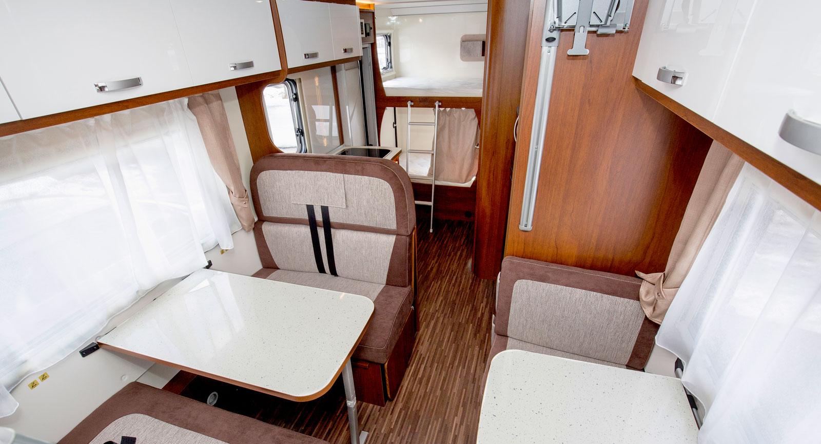 Mittskeppet på husbilen tas till stora delar upp av sittplatser medan köket är inrymt längre bak.
