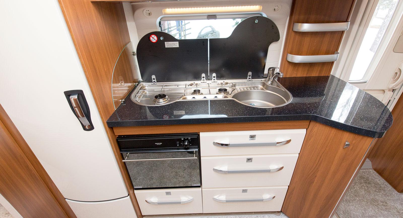 Föredömligt kök med gott om arbetsytor, delade lock till spis och diskho samt en gasolugn och massor av hyllor och lådor.