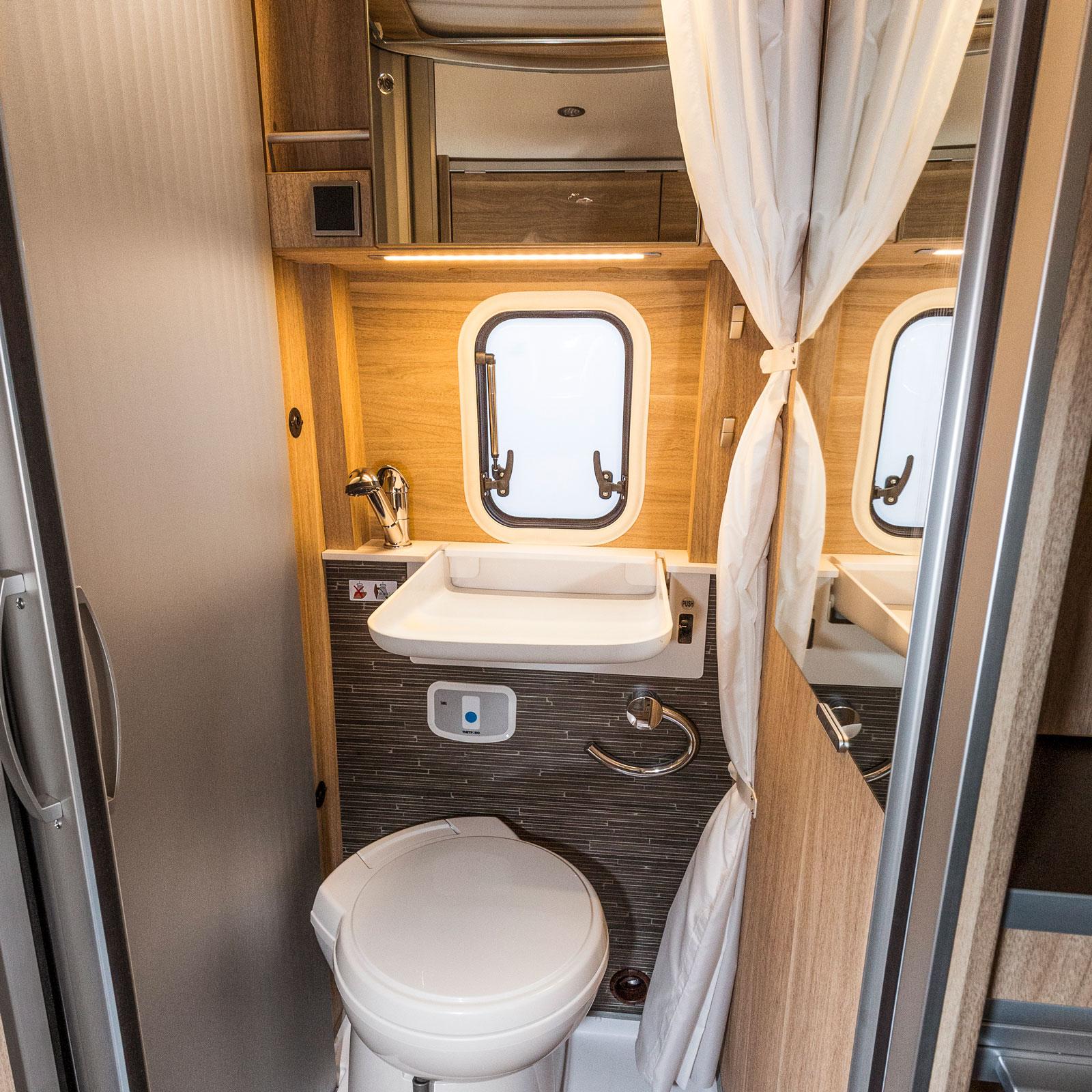 Ganska rymligt badrum för en liten bil. Handfatet kan fällas upp så det inte är i vägen vid toabesök. Duschkar finns under trallen.