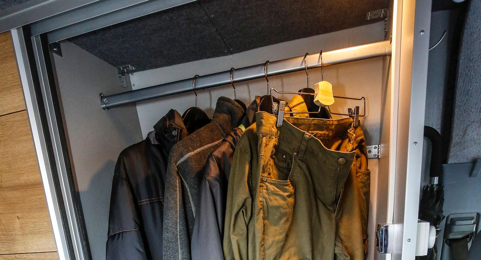 Bred garderob med skjutdörr till höger om toaletten.