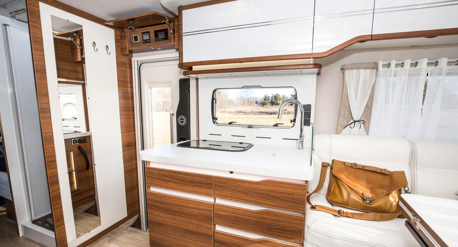 Entrén med helkroppsspegel samt två  krokar för ytterplagg. Notera även kökets propra och enhetliga design. Testbilen är extrautrustad med en exklusiv köksbänk av marmorliknande komposit.