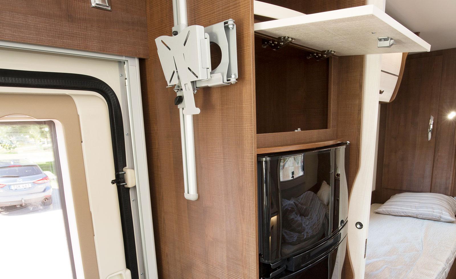 Entrédörren har fönster, skräpkorg och två låspunkter. Ledstång finns till hands. Tv-armen kan skjutas i höjdled på en skena.