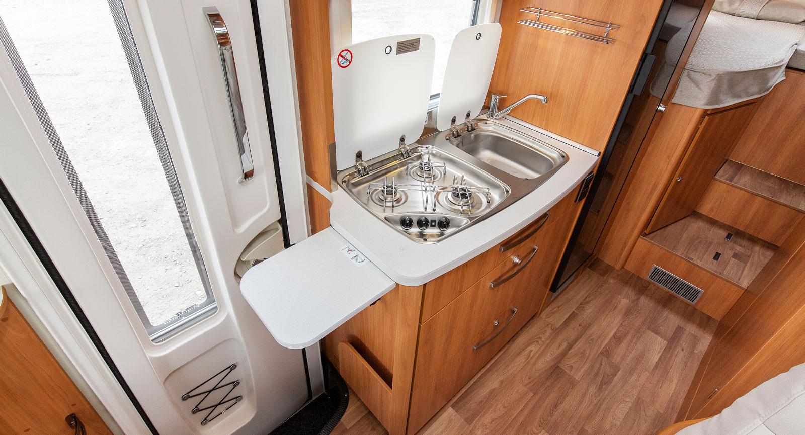 Köket är rakt och bänken upptas nästan helt av spis och diskho. Täckglas och extraskiva kan fällas upp vilket ger mer flexibilitet.