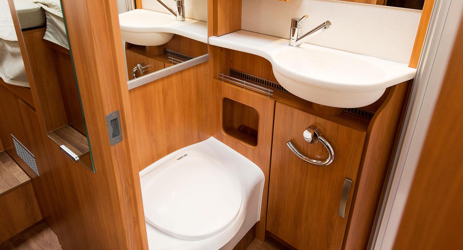 Mitt i bilen finns badrummet. Toalett av bänktyp, dusch med dörrar, förvaring och taklucka bildar ett funktionellt utrymme.