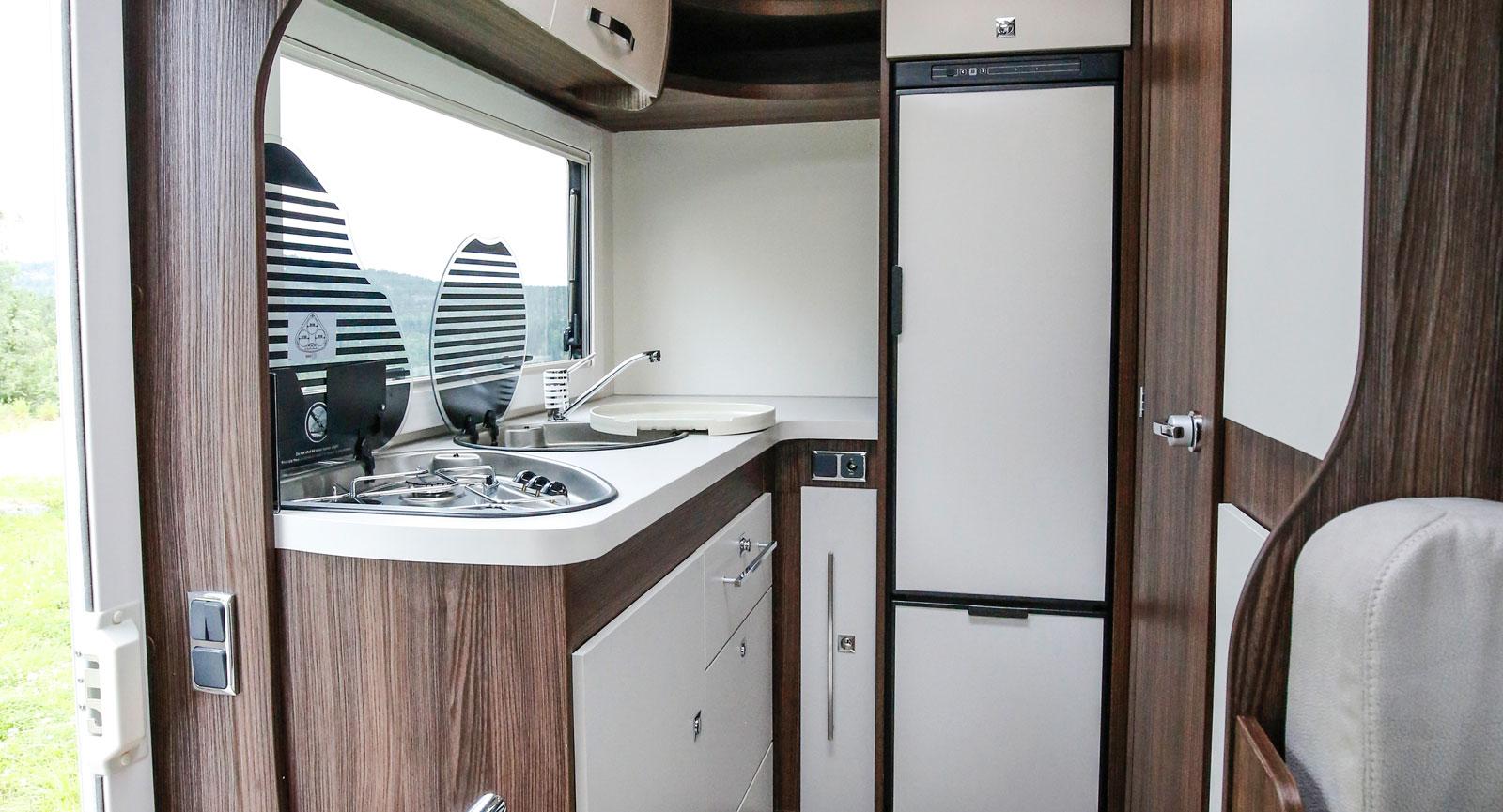 Trivsamt kök i bilens bakparti, dörren till toaletten till höger.