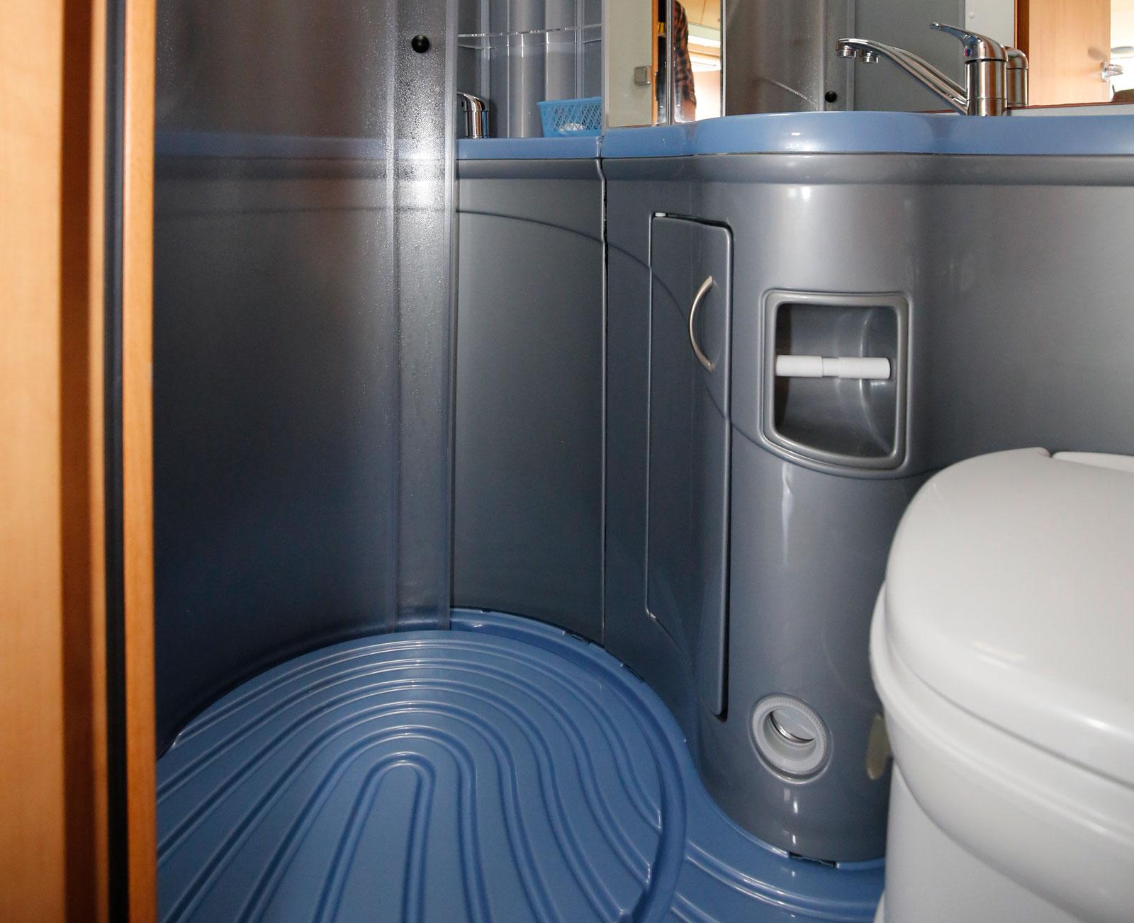 Duschkabin i form av en rörpostcylinder och ett i övrigt rätt plastigt badrum men för all del både praktiskt och rymligt.