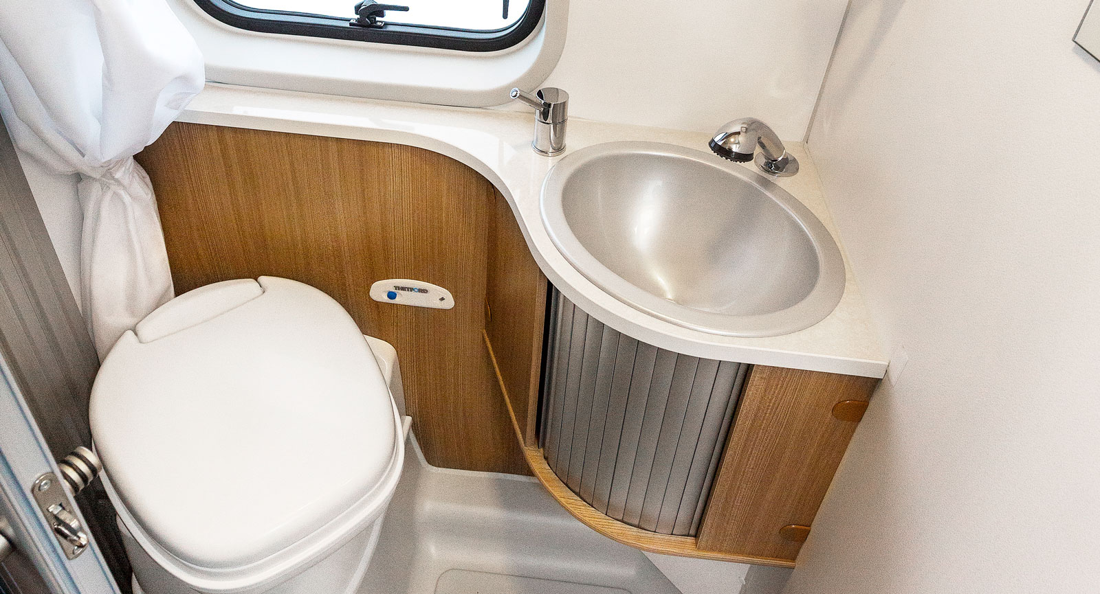 Hygienutrymmet har skjutdörr vilket är en vanlig  lösning i plåtisar.  Duschmunstycket fungerar som kran i handfatet.
