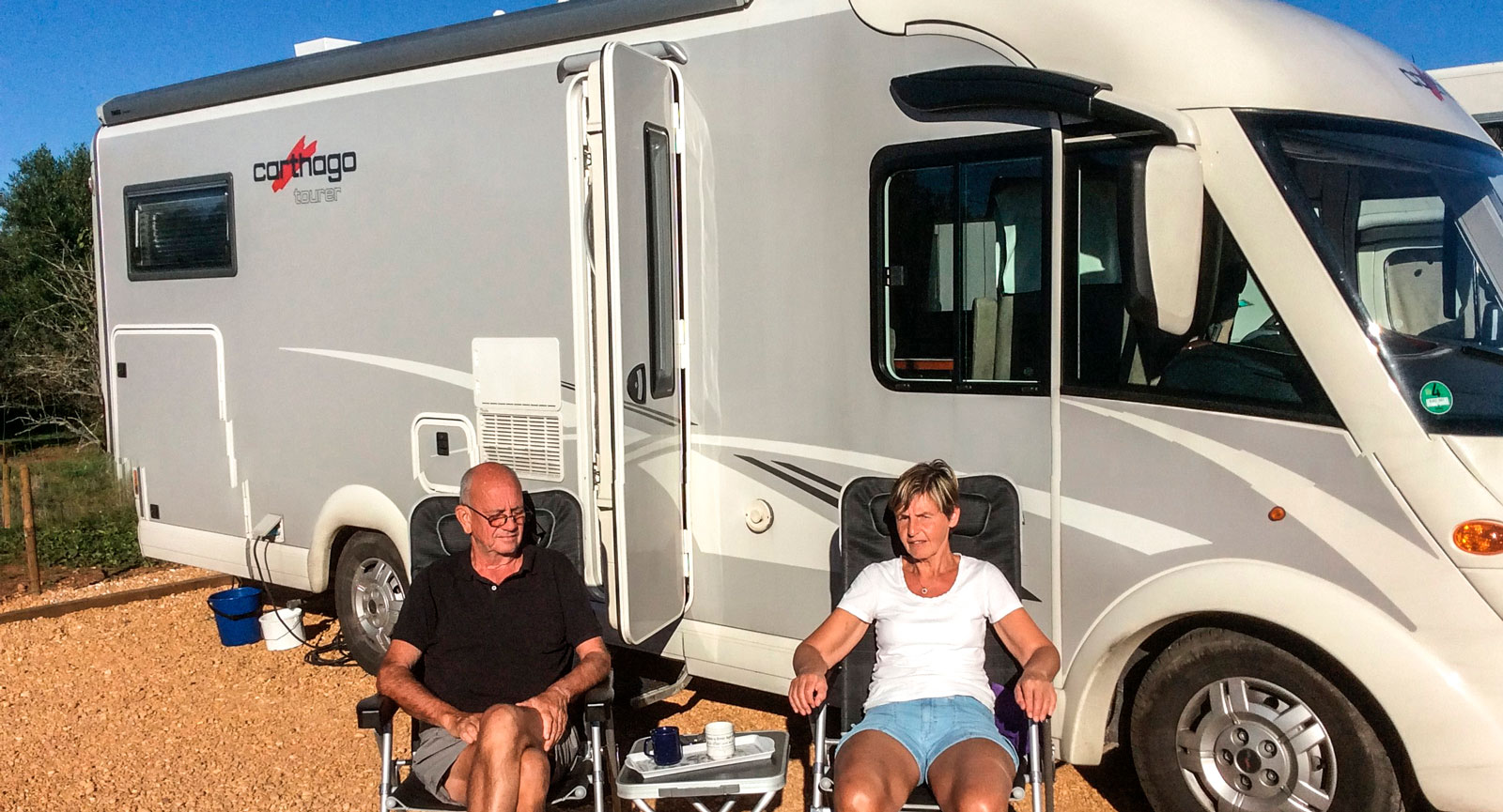 Lennart Nilsson och Britt-Inger njuter av eftermiddagssolen vid husbilen på Motorhome Park Silves längs Algarvekusten.