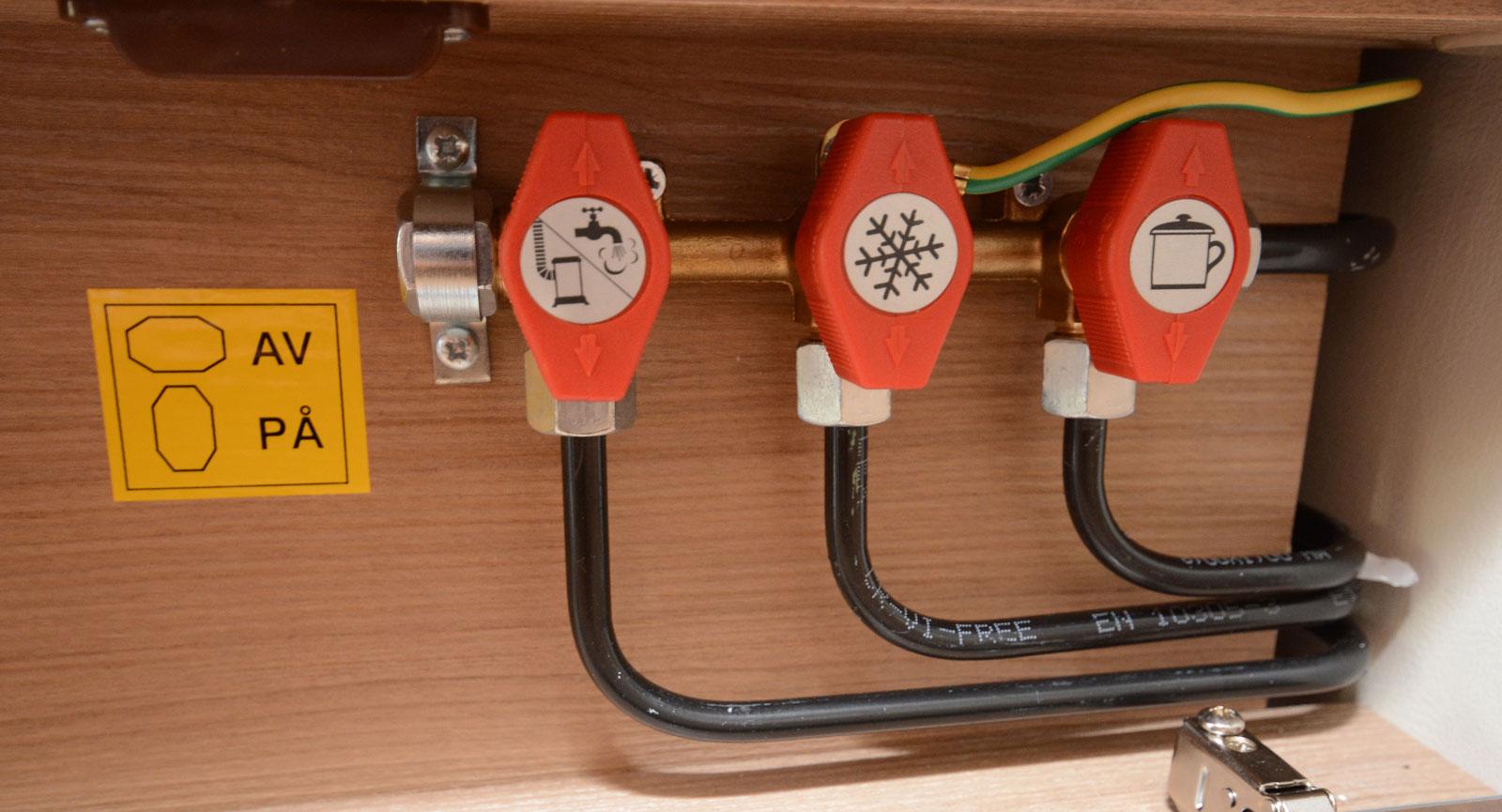 Avstängningsventiler till värme, kylskåp, och spis finns under kökslådorna.