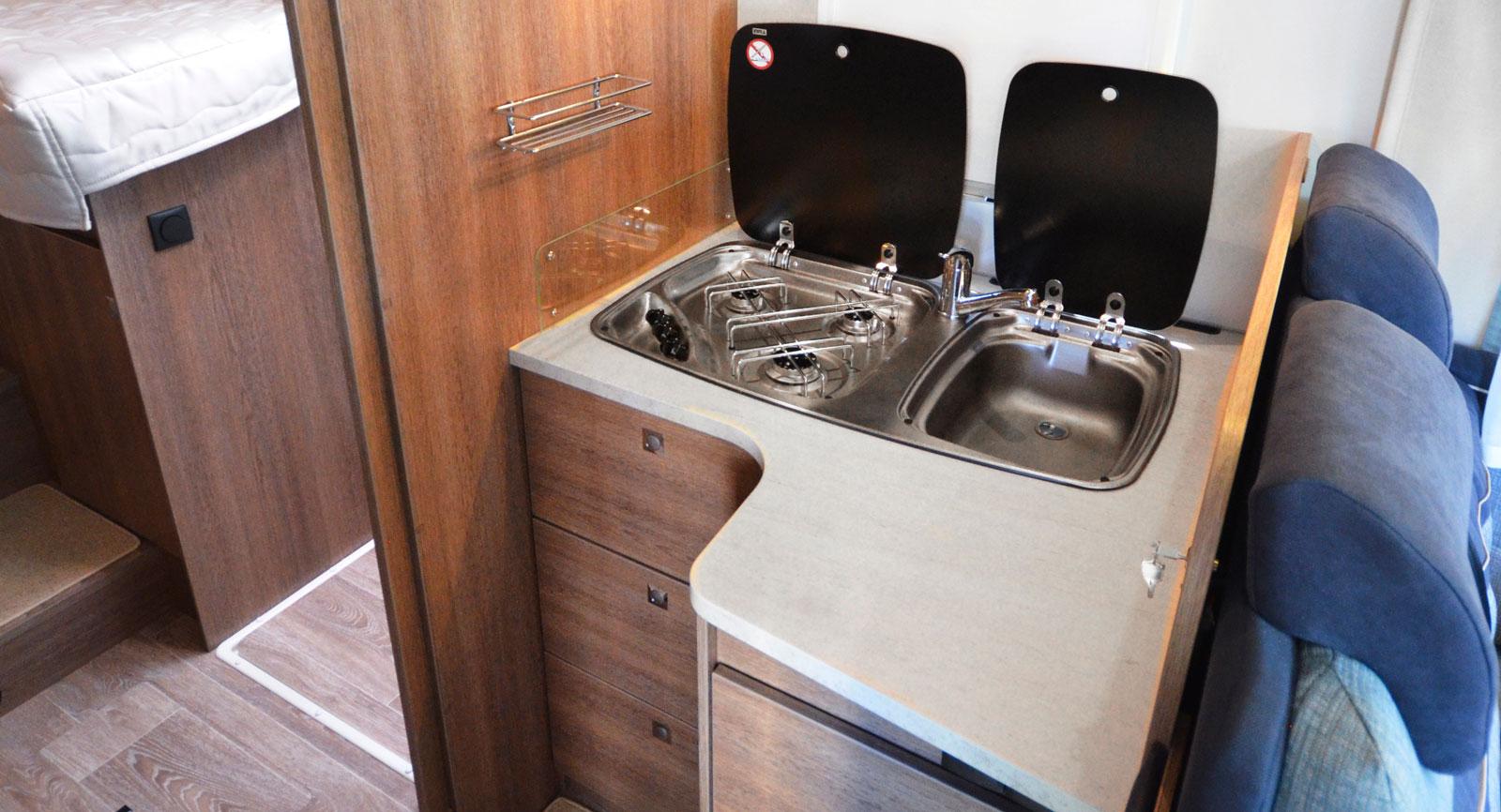 Köket är vinklat men har dåligt med förvaring. I det större  skåpet under köksbänken finns emellertid en sophink.