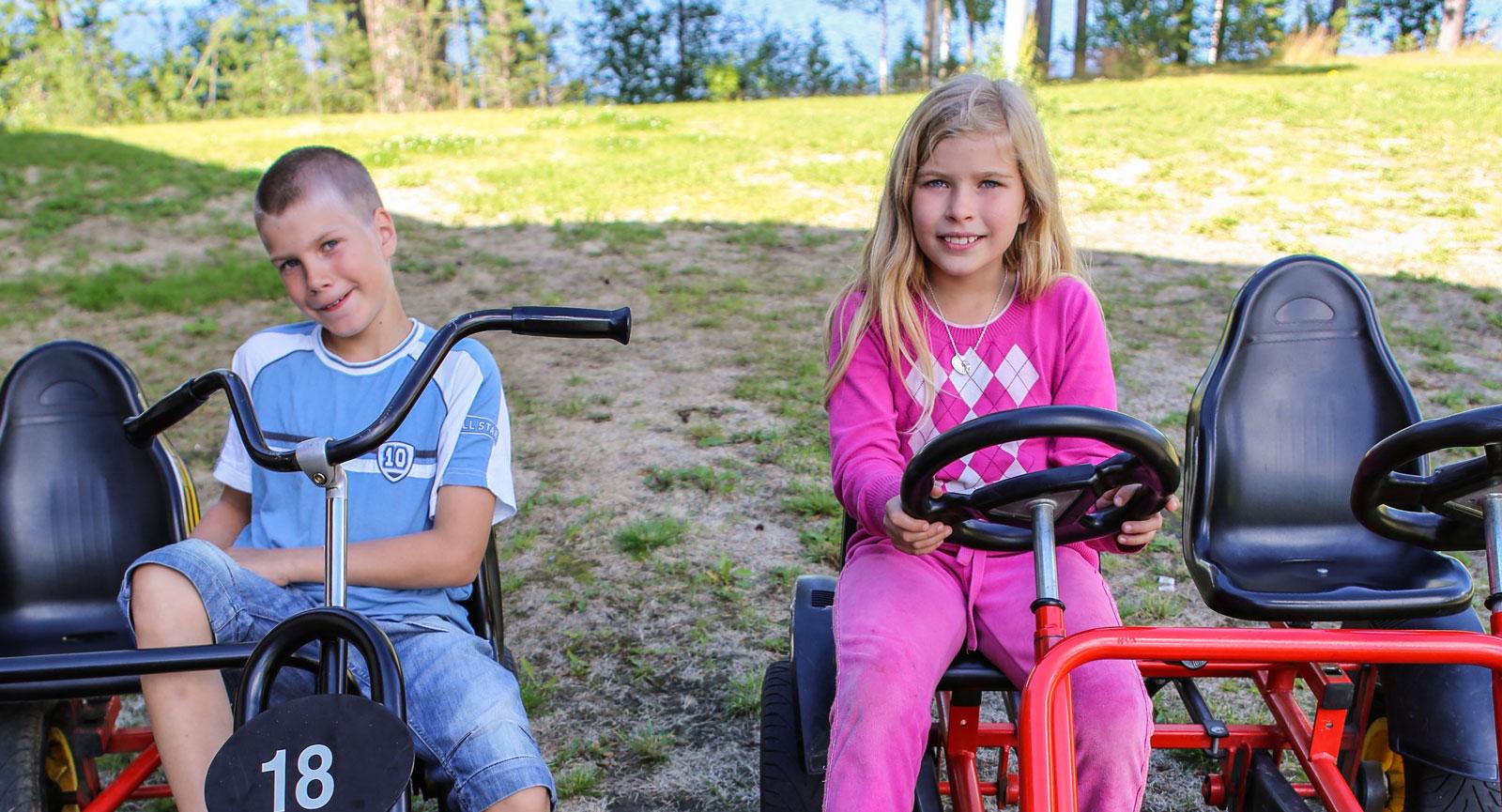 Syskonen Jesper och Jessie gillar trampbilarna som finns på området.