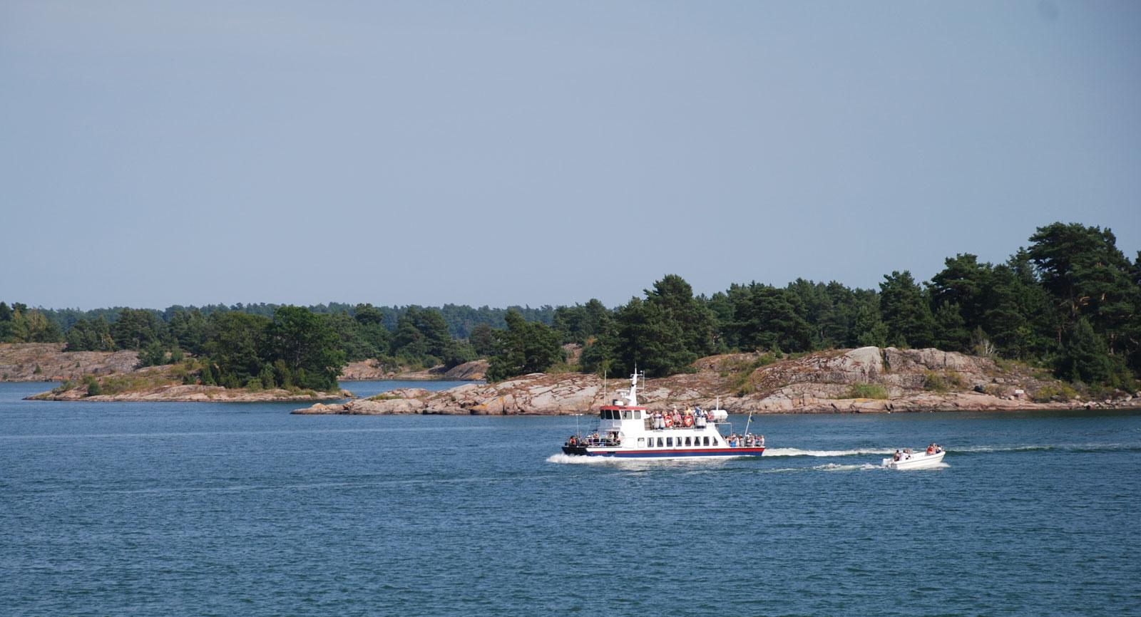 En av Skärgårdslinjens turbåtar passerar utanför campingen.