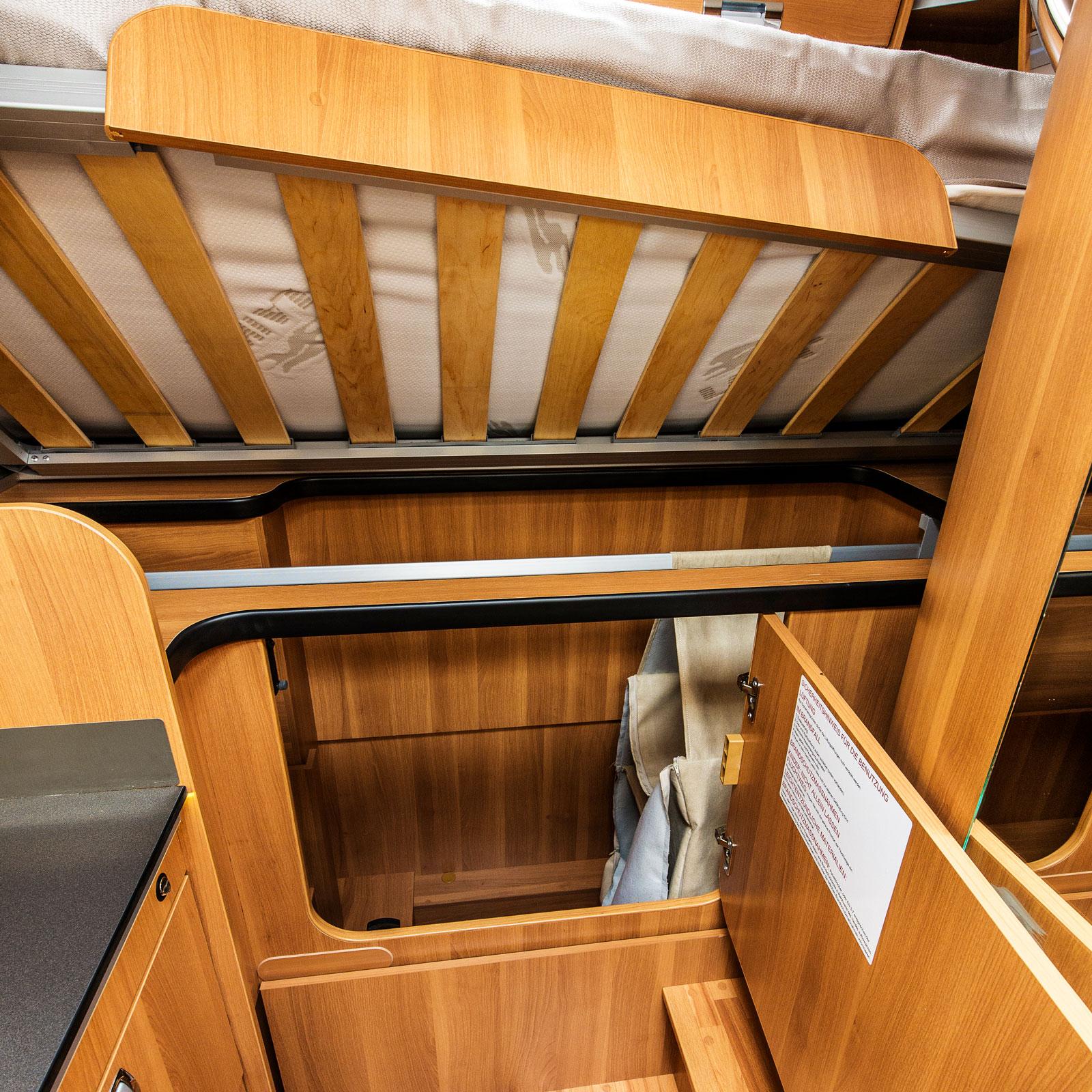 Under. Sängen har en garderob med klädstång under sig.
