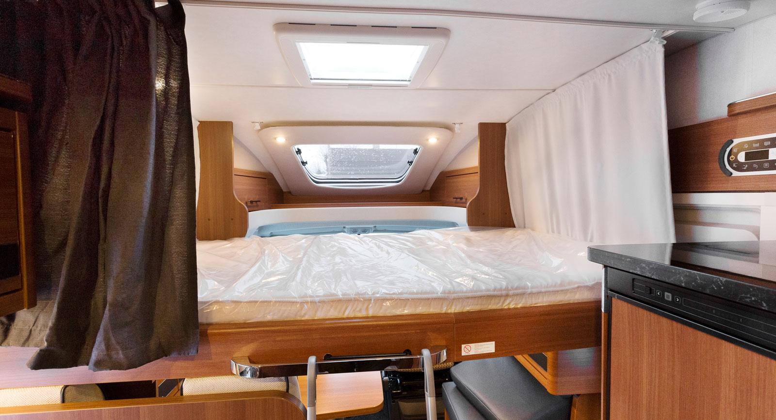 Bäddat. Sängen blockerar utgången vilket är mindre bra men vi gillar sovplatsen med mörkläggningsgardiner, takfönster, läslampor och direkt närhet till tv:n ovanpå kylskåpet till höger.