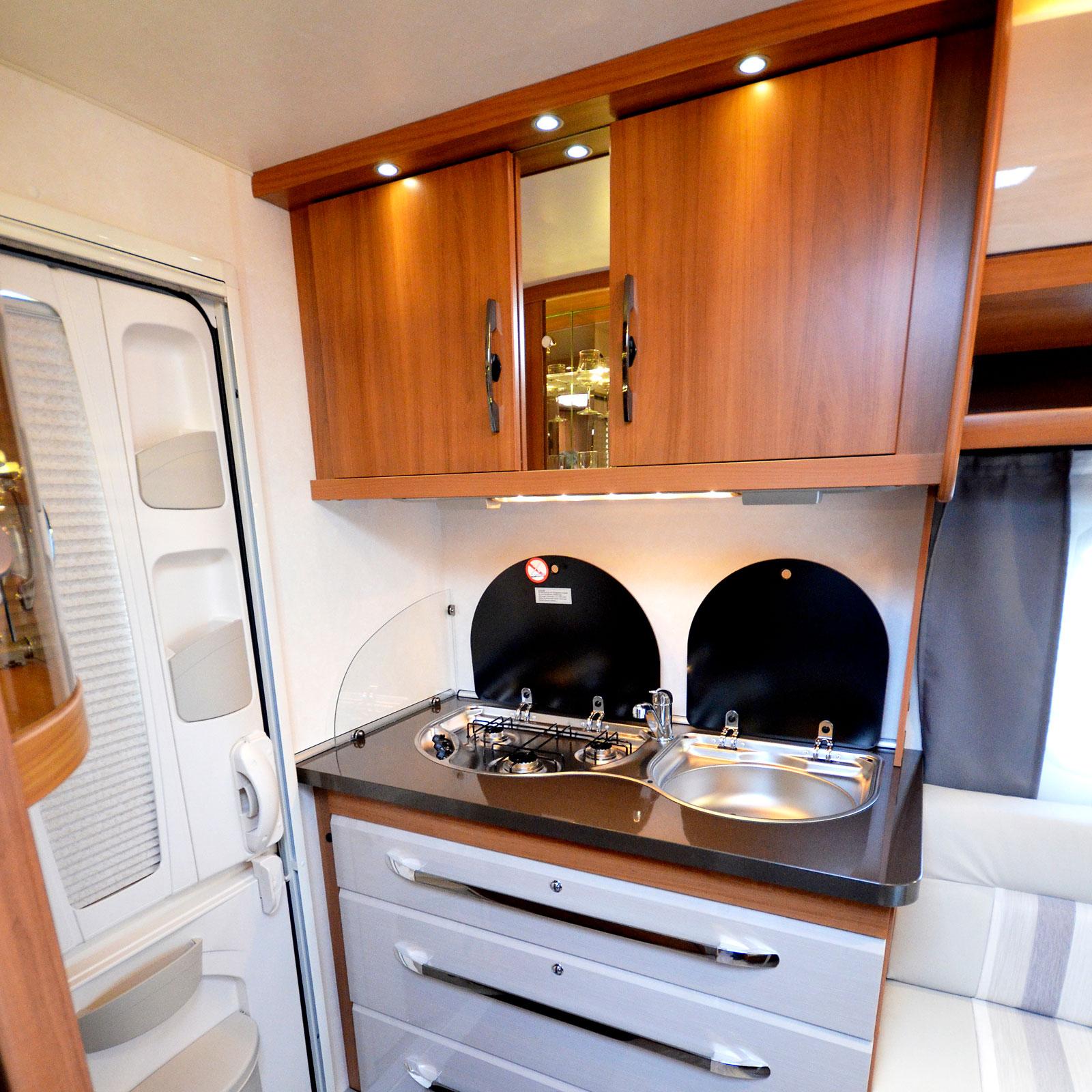 Välkommen. Entrén är placerad långt bak med köket till vänster. Det är tillräckligt med arbetsytor runt både diskhon och spisen.