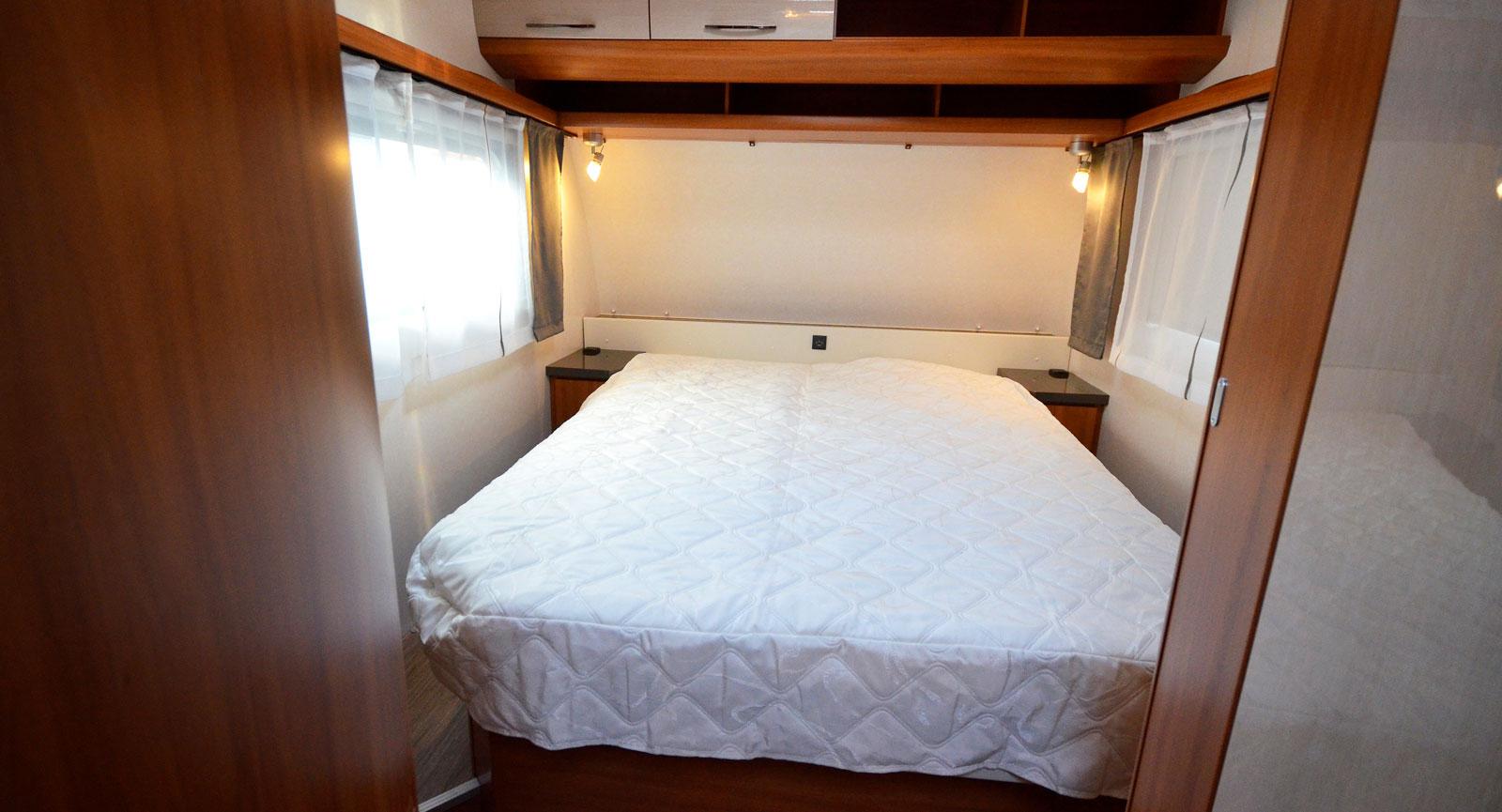 Trångt. På var sida om sängen är det 29 cm brett. På grund av gardinlisterna ovanför fönsterna känns det aningen trängre.
