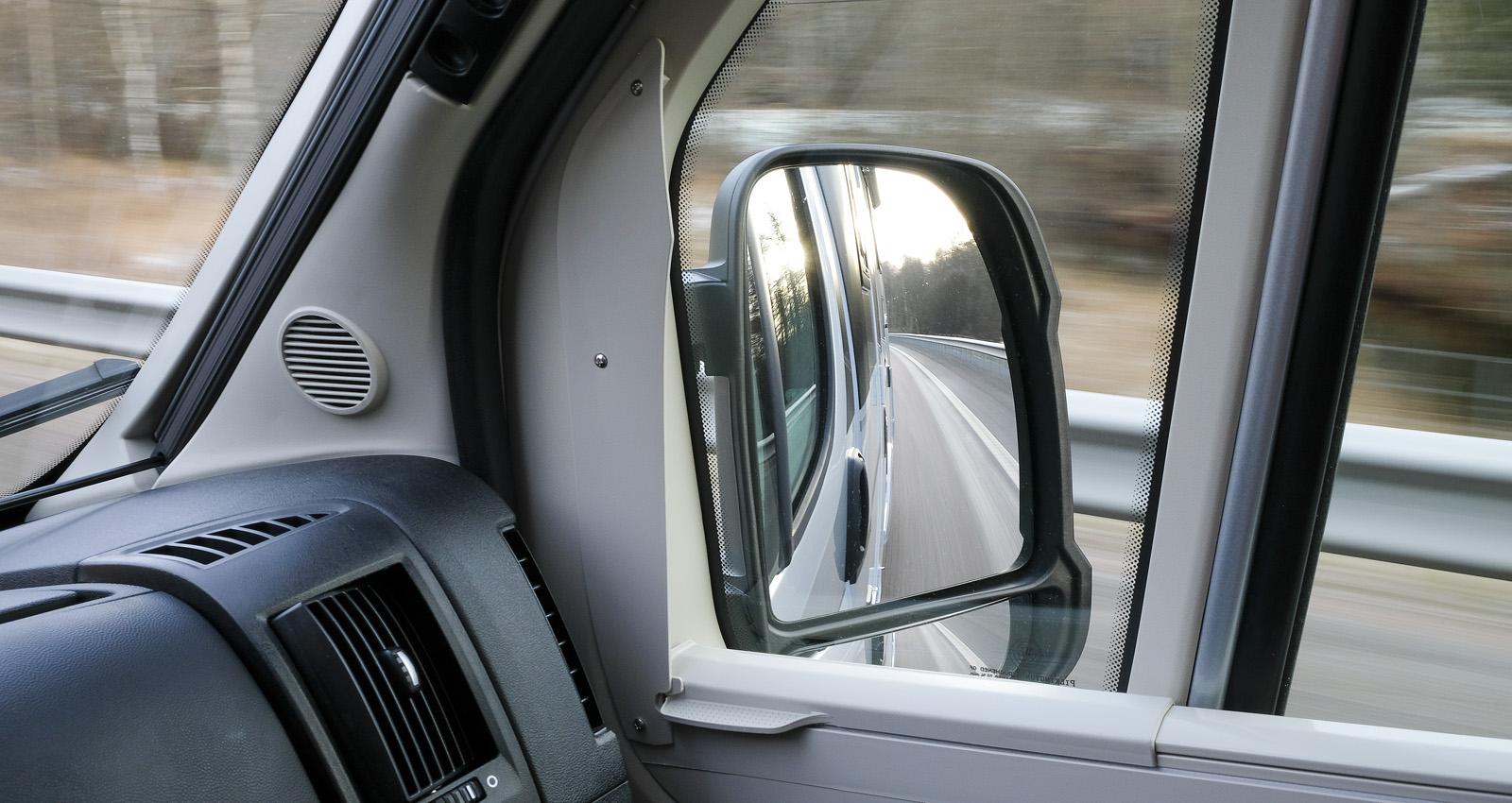 Sikten genom spegelns nedre del skyms av gardinkassetten.