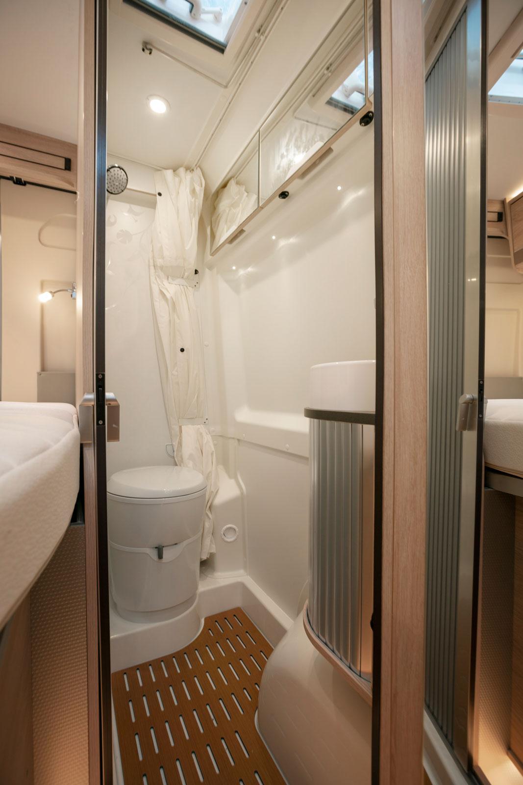 Långsmalt badrum med taklucka och draperi.