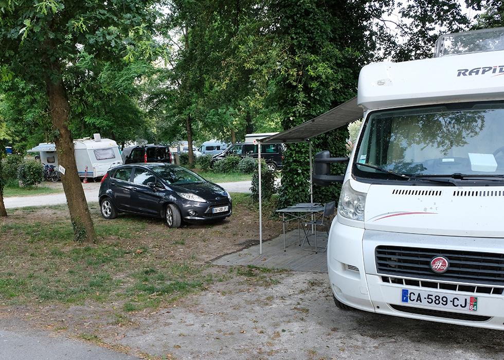 Mindre husbilar och tält står i nära anslutning till varandra.