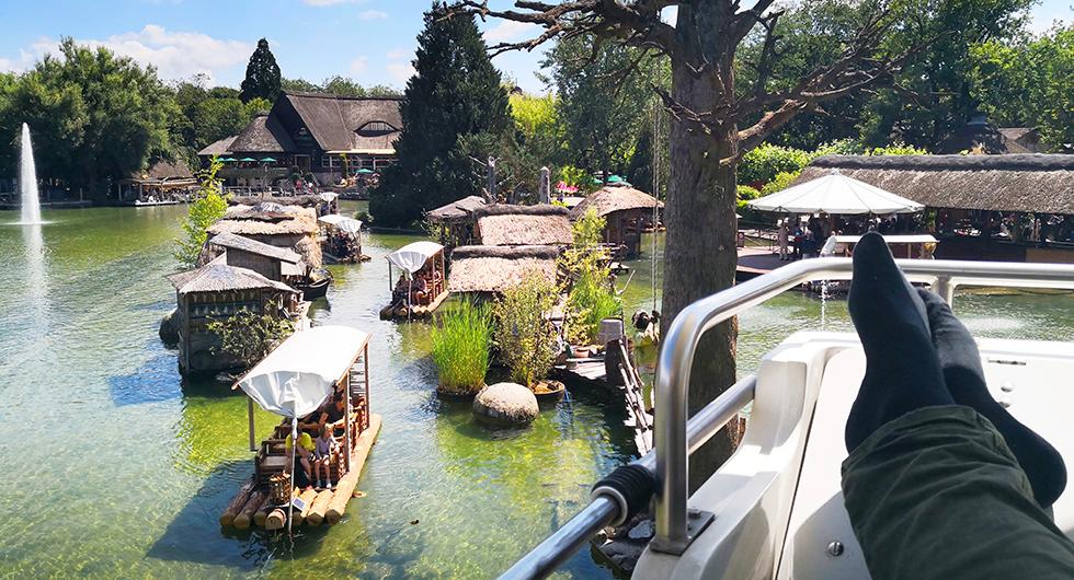 Öppen monorail med utsikt över Afrikas sjö som är full av plastflodhästar och båtar.
