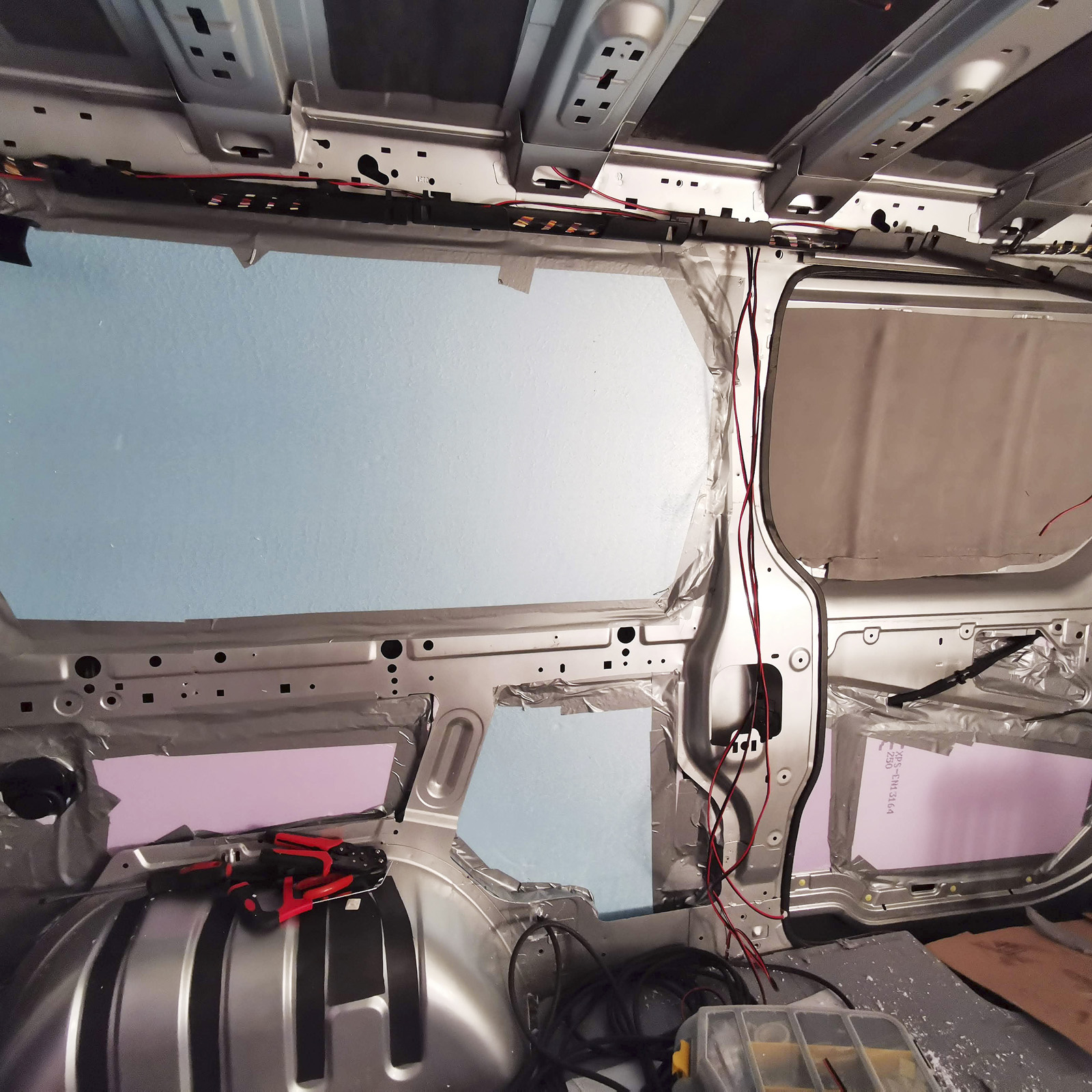 50 mm XPS i väggar och nederdel av skjutdörr, där utrymmet tillåter. Liggunderlag fästs med spraylim. Ett tips är att fotografera/mäta alla tvärbalkar och elkablar inför senare skruvning av väggar. (Egna träreglar att fästa i är också ett alternativ.)