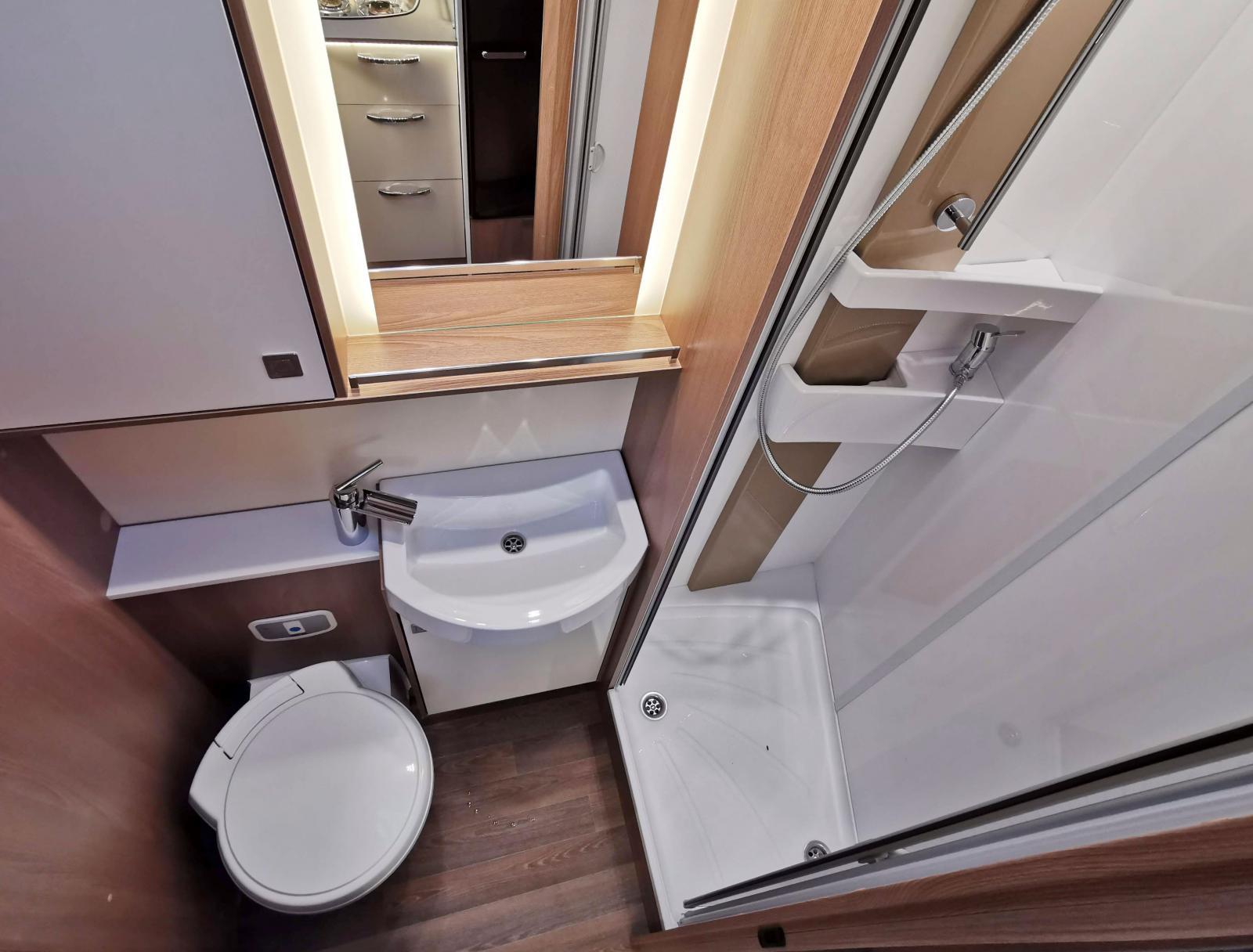 Komplett badrum i en och samma avdelning. Här finns det som behövs i form av förvaring och krokar. Bra med hyllor i duschen.