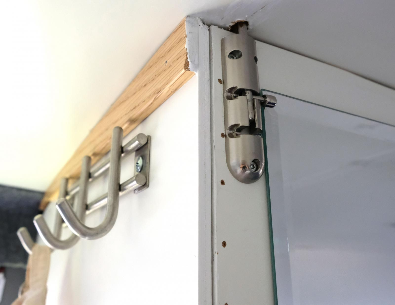 Till vänster vid entrén finns ett gäng krokar samt en garderob vars dörr hålls på plats med skjutregel.