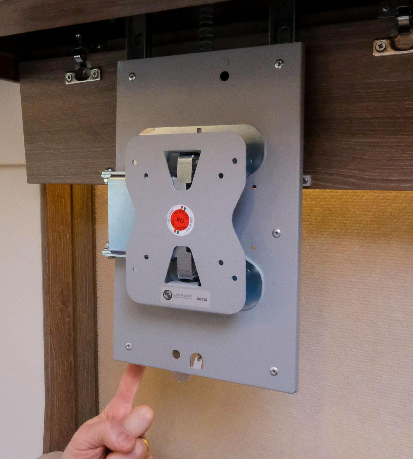Tv-stativ som fälls ned från överskåpet intill entrén.
