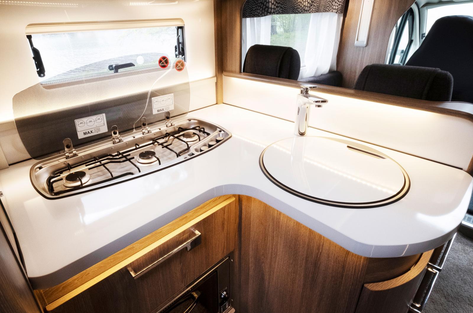 Ett ganska rejält kök för att vara en husbil och gott om avställningsyta framför spislågorna. Den glasliknande ytan är en illusion som utgörs av ett tunnt plastskickt på bänkskivan. Smart och lätt!