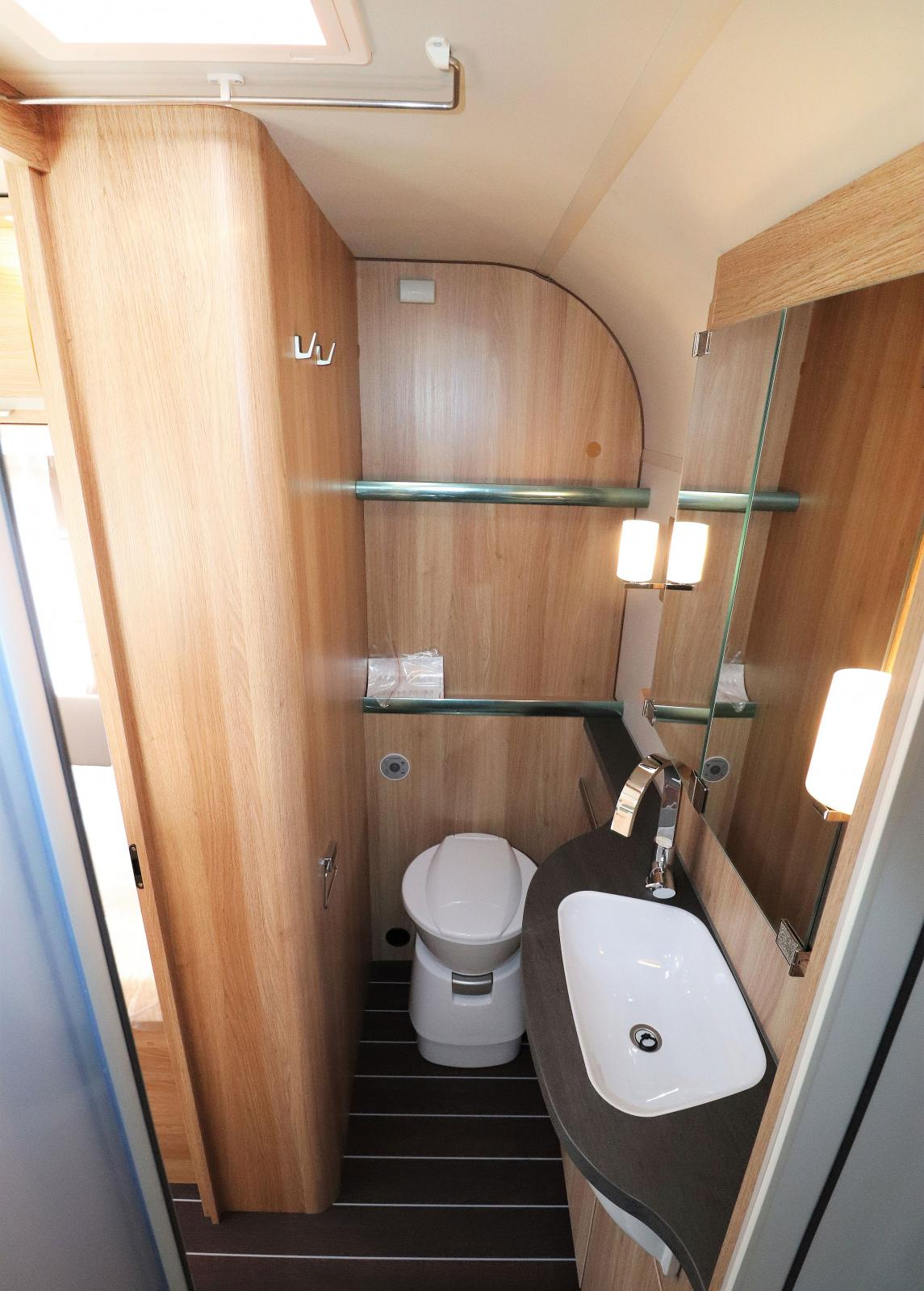 Ovanför toaletten finns två hyllor med liten kant. Bakom spegeln finns plats för mer förvaring.