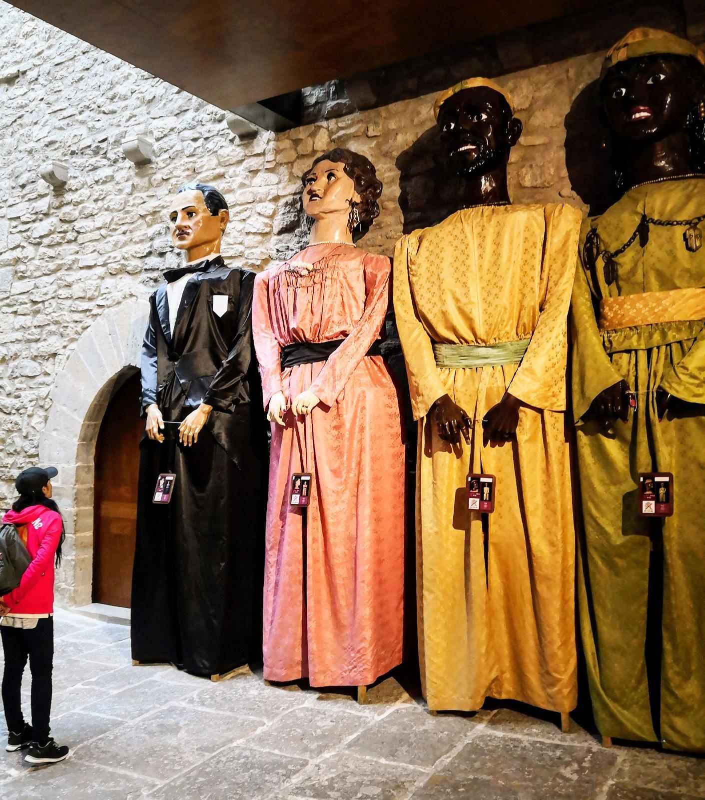 Jättelika dockor står och väntar på nästa procession genom staden.