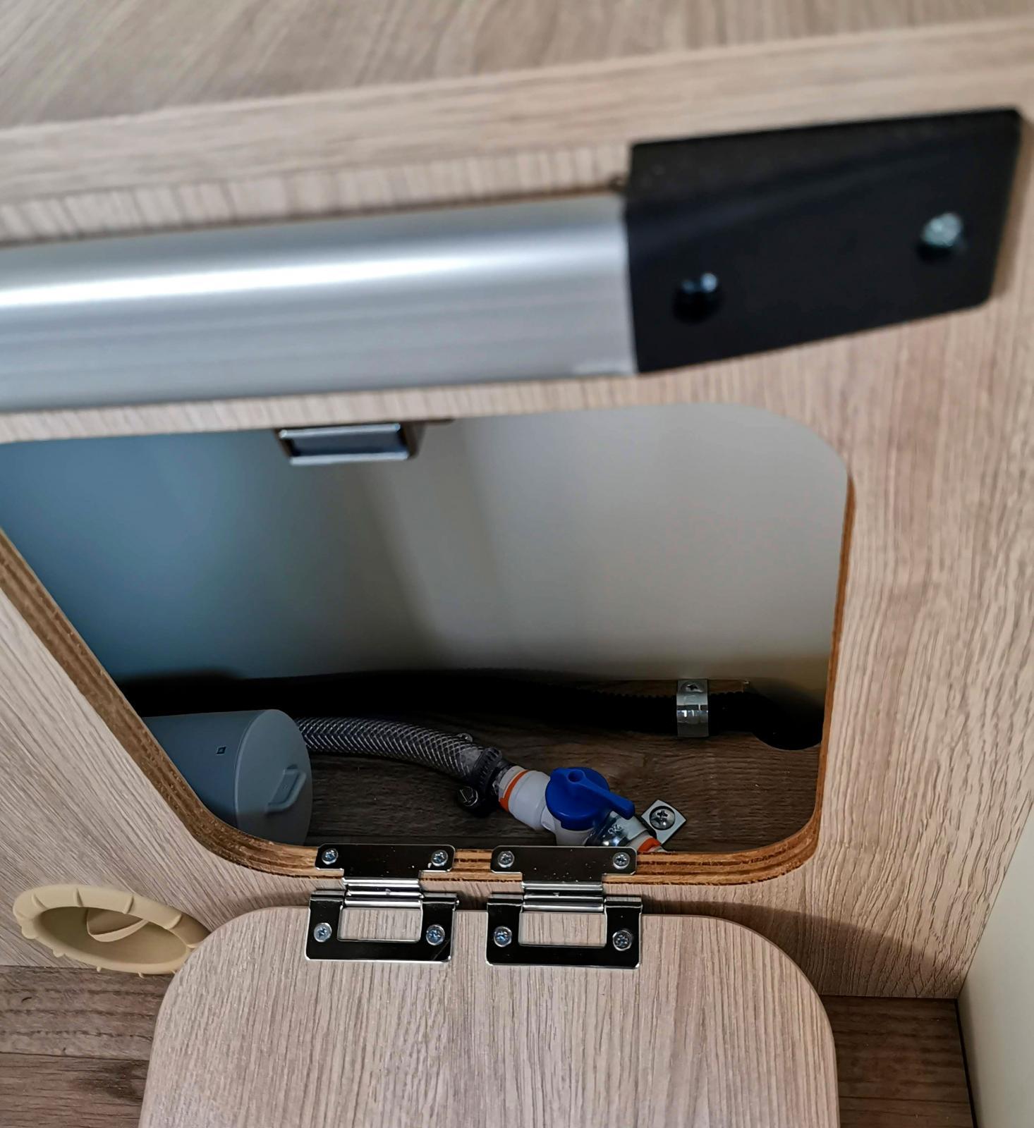 Kranen för tömning av varmvattenberedaren sitter under bordet.